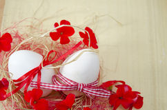 Two white eggs in a nest with red flowers Royalty Free Stock Image