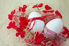 Two white eggs in a nest with red flowers Royalty Free Stock Photography