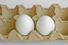 Two white eggs in the package for eggs from the chicken farm. Last egg stocks stock photography
