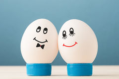 Two white eggs. With smiley faces, male and female royalty free stock photos