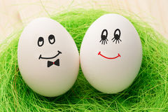 Two white eggs. With smiley faces, male and female stock photo