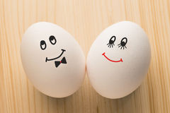 Two white eggs. With smiley faces, male and female royalty free stock photo