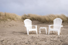 Two, white and empty adirondack chairs on sand dunes in beach Stock Photography