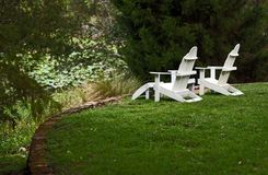 Two white empty chairs facing pond with lilies Royalty Free Stock Photos