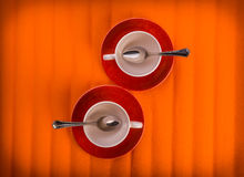 Two white empty cups with tea spoons, on red plates over orange color background, view from above Stock Photo