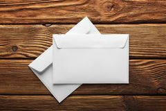 Two white envelopes with letters on old wooden dark background. Blanks for the designer. Concepts, ideas for postal services and e royalty free stock photo