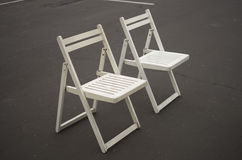 Two white folding chairs Stock Photos