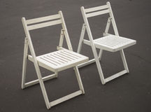Two white folding chairs Royalty Free Stock Photos