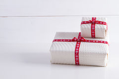 Two white gift boxes with polka dots  a red ribbon. Stock Photo