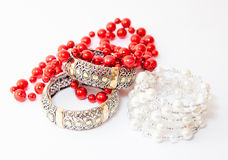 Two white gold bracelets and red necklace Stock Images