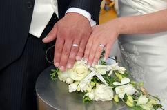 Two white gold wedding rings on roses bouquet Stock Photos