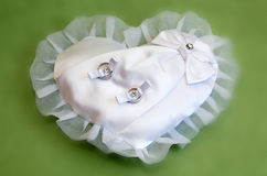 Two white gold wedding rings on white heart lace pad Stock Photo