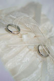 Two white gold wedding rings on white lace pad Royalty Free Stock Photography