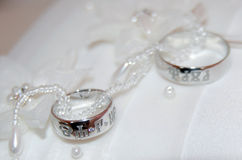 Two white gold wedding rings on white lace pad Stock Photography