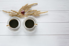 Two white and golden cups of coffee with decorative golden branches and small glass and red heart on white wooden background. Two white and golden cups of coffee Royalty Free Stock Photos