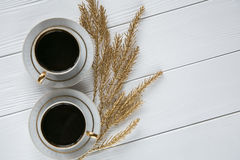 Two white and golden cups of coffee with decorative golden branches and small glass on white wooden background. Space for text Stock Photos