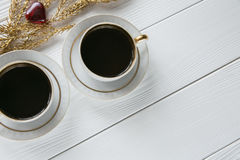 Two white and golden cups of coffee with decorative golden branches on white wooden background. Two white and golden cups of coffee with decorative golden Stock Photography
