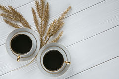 Two white and golden cups of coffee with decorative golden branches on white wooden background. Space for text Royalty Free Stock Photos