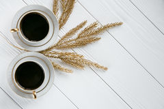 Two white and golden cups of coffee with decorative golden branches on white wooden background. Space for text Royalty Free Stock Photo