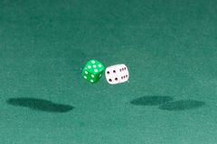 Two white and green dices falling on a green table. Two white and green dices falling on a isolated green table royalty free stock image
