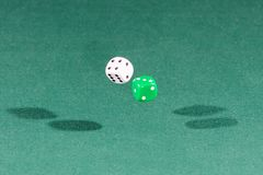 Two white and green dices falling on a green table. Two white and green dices falling on a isolated green table royalty free stock photography