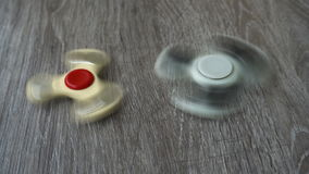 Two white hand spinner spinning on grey background or fidget spinners stock video