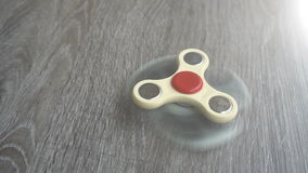 Two white hand spinner spinning on grey background or fidget spinners.  stock video