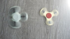 Two white hand spinner spinning on grey background or fidget spinners.  stock footage