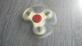 Two white hand spinner spinning on grey background or fidget spinners stock footage
