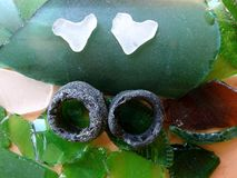 Different sea glass pieces - rind and heart , Lithuania. Two white heart and two rings found in Baltic sea royalty free stock photography