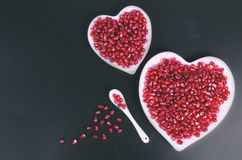 Two white heart shaped plates full of fresh juicy pomegranate seeds, little spoon, whole fruit and ripe one. Toned. Two white heart shaped plates full of fresh Royalty Free Stock Photography