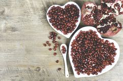 Two white heart shaped plates full of fresh juicy pomegranate seeds, little spoon, whole fruit and ripe one. Toned. Royalty Free Stock Photography