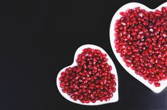 Two white heart shaped plates full of fresh juicy pomegranate seeds, little spoon, whole fruit and ripe one. Toned. Royalty Free Stock Photo