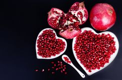 Two white heart shaped plates full of fresh juicy pomegranate seeds, little spoon, whole fruit and ripe one. Toned. Royalty Free Stock Image