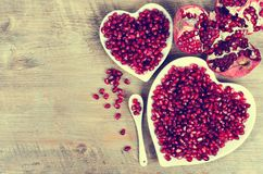 Two white heart shaped plates full of fresh juicy pomegranate seeds, little spoon, whole fruit and ripe one. Toned. Two white heart shaped plates full of fresh Royalty Free Stock Images