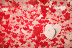 Two white hearts. On a background full of red hearts with shallow depth of field Royalty Free Stock Images