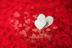 Two white hearts. On a background full of red hearts with shallow depth of field Stock Photos