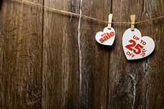 Two white hearts and discounts with romantic pattern on wooden background. Big sale in one heart. And twenty-five percent on another hanging on rope by royalty free stock image