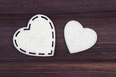 Two white hearts of felt on a brown wooden background. Valentine Day. Greeting Card. Royalty Free Stock Photos