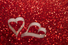 Two white hearts from paper on red shining background  blurred Stock Images