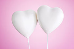 Two white hearts on pink background stock photography