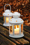 Two white lanterns on wooden bench Stock Photos