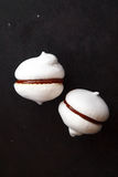 Two white meringue cookies with chocolate on black background. Two white meringue cookies on black background Royalty Free Stock Photo