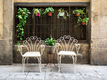 Two white metal chairs in the old town of Barcelona Royalty Free Stock Photos