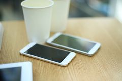 Two white mobile phones with tablet on wooden table background, blank screen electronic device with copy space. Two white mobile phones with tablet on wooden Royalty Free Stock Photo