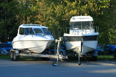 Two white motor boats on trailers. Powerboats on transport trailers stand in the shade on the beach in evening time. Front view Stock Photography