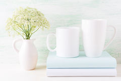 Two white mugs mockup with books and white flowers in pitcher Royalty Free Stock Photo
