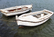 Two white old boats in the middle of the water Royalty Free Stock Photos
