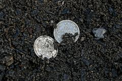 Two white old silver coins lying in black earth royalty free stock photography