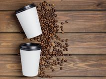 Two white paper cups and coffee beans on old brown wooden background. top view stock image